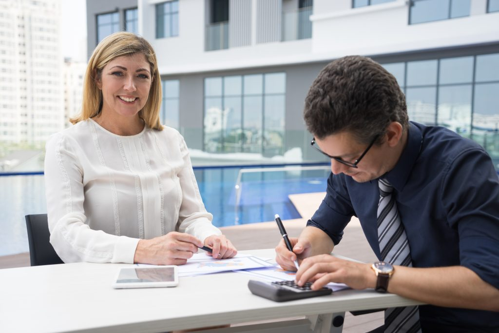 Cheerful excited mature female financier smiling at camera while accountant using calculator in outdoor business cafe. Successful business executive meeting with financial advisor. Informal meeting concept