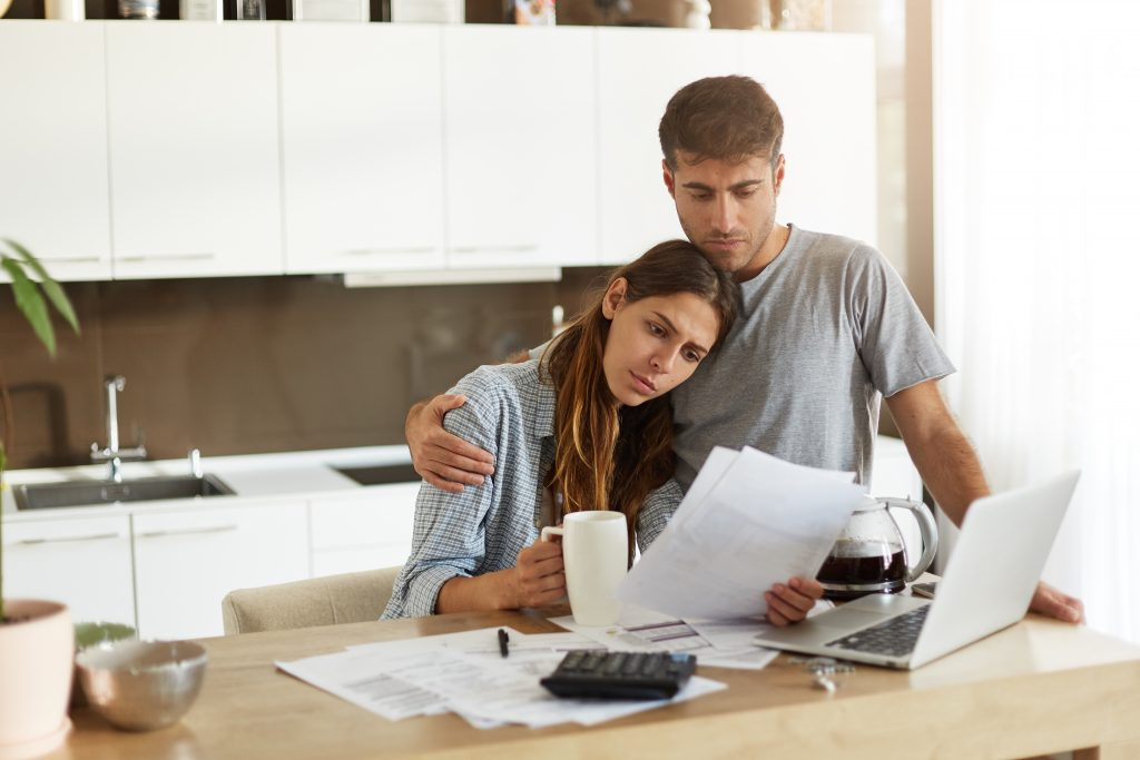 Unhappy young European family facing financial troubles: sad husband deep in thoughts hugging his worried wife who is studying notification from bank in her hands while doing finances in kitchen
