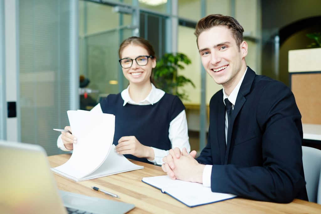 Young bankers working with papers and reading contracts in office